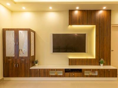 یک میز تی وی قهوه ای زنگ بزرگ که یک صفحه تلویزیون در داخل آن نصب شده است و دارای باکس های افقی و عمودی بوده و در اطراف آن نورپردازی شده است