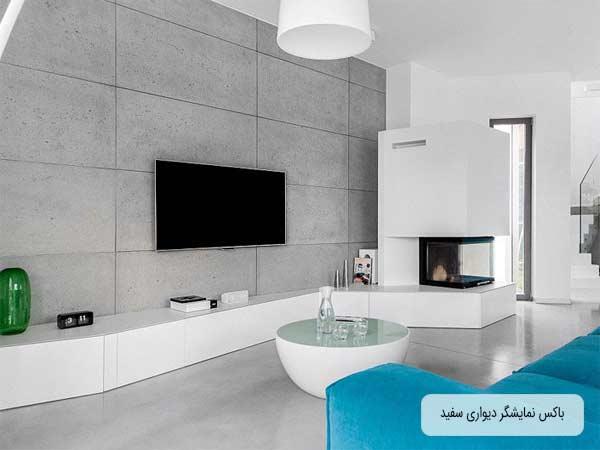 میز زیر تلویزیونی دیواری ساده سفید در عکس قرار دارد که تلویزیون بر روی دیوار پشتی طوسی رنگ متصل شده است و بر روی میز زیر تلویزیونی لوازم جانبی چیدمان شده ات و یک شومینه داخل باکس سفید قرار دارد.