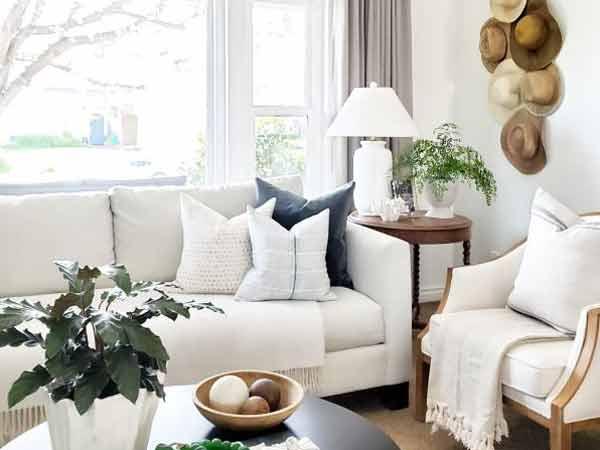 مبلمان راحتی سفید رنگی در اتاق نشیمن با دسته چوبی قهوه ای رنگ در تصویر قرار دارند که روی آن ها چند کوسن سفید و یک کوسن مشکی و دو پتو سفید قرار دارد و کنار آن یک میز عسلی چوبی به رنگ قهوه ای تیره می باشد که روی آن یک آباژور سفید و گلدان سفید می باشد و پشت میز عسلی پرده خاکستری رنگ و پنجره سفید می باشد و روبه روی مبلمان راحتی نیز یک میز جلو مبلی قرار دارد که روی آن یک ظرف قهوه ای رنگ و یک گلدان سفید رنگ می باشد و بر روی دیوار کناری آن چندین کلاه ه روی دیوار متصل شده است