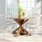 یک میز ناهار خوری گرد چوبی به رنگ قهوه ای با چهار صندلی چوبی سفید و دو گلدان