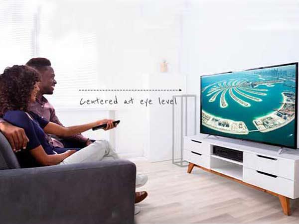 یک زن و مرد سیاه پوست بر روی کاناپه بنفش رنگی نشسته اند و به تی وی نگاه می کنند و صفحه نمایشگر به روی میز زیر تلویزیونی سفیدی قرار گرفته است.