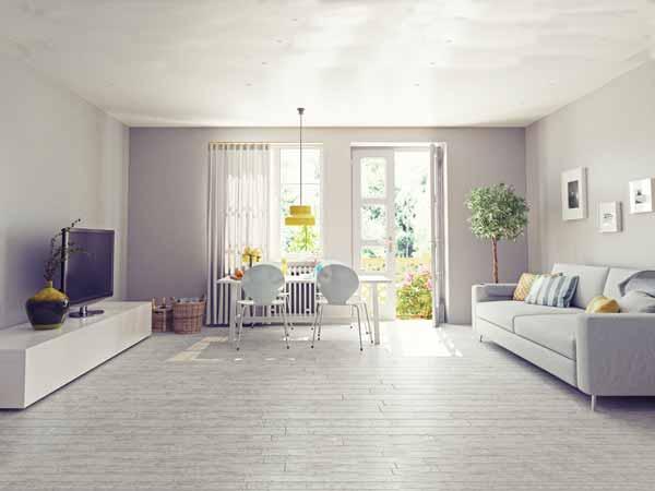 اتاق نشیمنی با دیواره ای به رنگ یاسی و یک میز تلویزیون سفید که نمایشگر روی آن قرار گرفته است و یک گلدان با ترکیب رنگ های مشکی و سبز و زرد کنار تلویزیون می باشد و یک مبل راحتی خاکستری همراه با کوسن هایی به روی آن در تصویر می باشد و یک در سفید نیمه باز که کنار آن میز ناهارخوری و دو صندلی سفید در اتاق قرار گرفته است