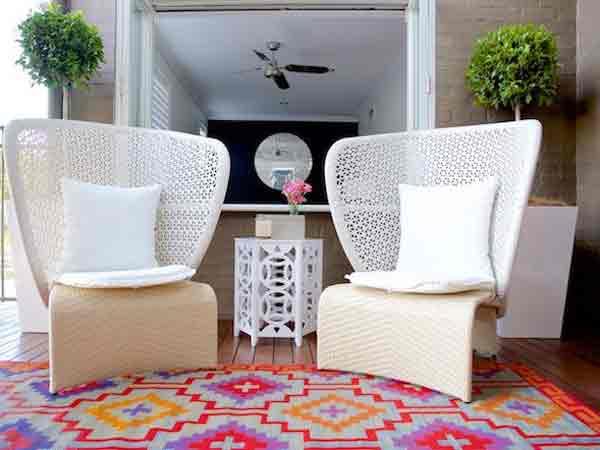 در تصویر دو صندلی یکسان و متقارن با ترکیب رنگی سفید و کرم می باشد که هر دو دارای کوسنی به رنگ سفید هستند و کف زمین به صورت پارکت است و رذوی آن یک فرش طرح دار با ترکیب ترکیب های رنگ های قرمز و بنفش و سبز و نارنجی تشکیل شده است و یک میز عسلی چوبی سفید بین این دو صندلی قرار گرفته است که روی با لوازم تزیینی چیدمان شده است