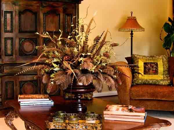 یک گلدان بزرگ با بدنه طرح دار چوبی بر روی یک میز جلو مبلی چوبی قرار گرفته است که کنار آن چندین کتاب بر روی همخ قرار دارند و یک سینی طرح دار همراه با لیوان هایی طرح دار داخل آن بر روی میز جلو مبلی قرار دارد و در این فضای اتاق یک کمد چوبی بزرگ به رنگ قهوه ای سوحتع نیز می باشد و یک مبل راحتی قهوه ای با کوسنی بر روی آن با ترکیب رنگ های سبز و زرد و مشکی می باشد و یک اباژور پشت آن قرار گرفته است
