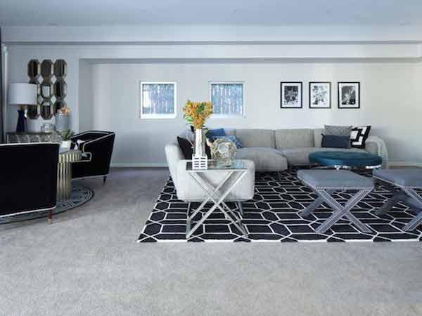 فضای داخلی منزل را در تصویر نشان می دهد که دارای تعدادی مبلمان راحتی به رنگ های خاکستری و مشکی می باشد و روی دیوار های فضای اتاق تعدادی تابلو و اثر هنری نصب شده است و کف زمین اتاق به صورت موکتی خاکستری می باشد و یک فرش طرح دار با ترکیب رنگ های سفید مشکی قرار دارد