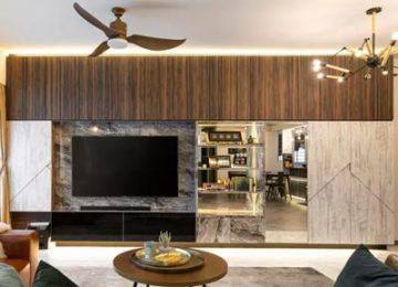 یک باکس تی وی دیواری مدرن با دیوار پشتی سرامیک خاکستری همراه با دیواره چوبی و شیشه ای می باشد که دارای کشو هایی با رنگ مشکی نیز می باشد و صفحه نمایشگر در وسط ذیواره سرامیکی نصب شده است و اتاق نشیمن دارای یک پنکه سقفی قهوه اغی رنگ نیز می باشد و یک میز گرد مانند چوبی به رنگ قهوه ای روشن روبه روی تی وی قرار دارد.