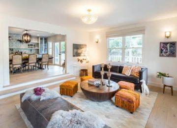 فضای داخلی یک منزل را تصویر نشان می دهد که در آن یک مبل راحتی مشکی با کوسن های طرح دار با ترکیب رنگی نارنجی سفید قرار گرفته است و یک میز جلو مبلی چوبی روبه روی آن می باشد و دور آن میز های عسلی با ترکیب رنگی زرد نارنجی قرمز و صورتی قرار گرفته است و روی میز جلو مبلی با لوازم تزیینی پر شده است و از سقف آن یک لوستر نورانی کوتاه قرار گرفته است ودر طرف دیگر یک میز ناهار خوری همره با صندلی های دورش که به رنگ سفید طوسی می باشد قرار گرفته است و بالای آن یک لوستر دایره ای مانند مشکی می باشد و دیواره پشت میز ناهار خوری به رنگ ابی روشن و رگه های سفید می باشد.