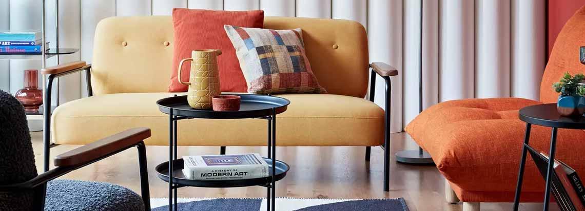 اتاقی با یک دست مبل با ترکیب رنگ نارنجی و زرد به همراه فرش سورمه ای سفید و صندلی سورمه ای و کتابخانه ای در گوشه آن
