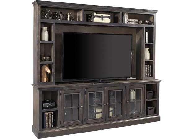 میز تی وی صندوقی به رنگ قهوه ای سوخته در تصویر جزء یکی از چیدمان های منزل می باشد که صفحه نمکایشگر سیاه در مرکز آن قرار گرفته است این میز به صورت قفسه باز و کابینتی می باشد که در داخل آن ها با وسایل جانبی پر شده است.