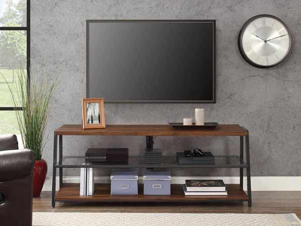 یک میز تلویزیون فلزی با ترکیبی از لایه چوبی به رنگ قهوه ای تیره می باشد و صفحه نمایشگر بالای میز به دیوار پشتی طوسی رنگی که دارد متصل شده است و یک ساعت در کنار تی وی دیده می شود. و یک قاب عکس و دو عدد شمع نیز روی میز تی وی قرار دارد.