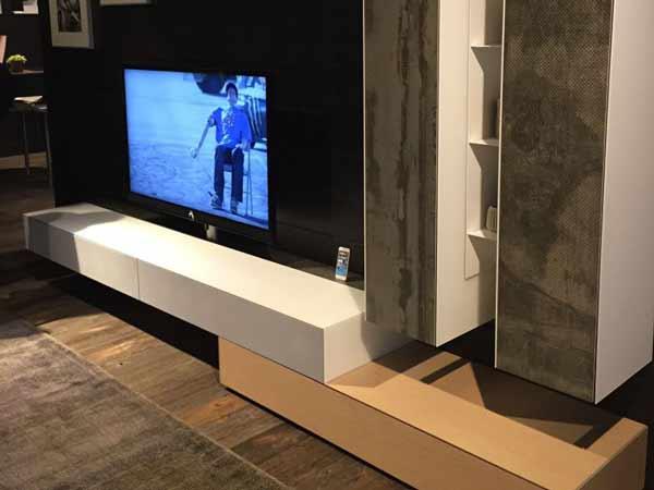 میز تی وی مدرنی در دکوراسیون داخلی خانه با ترکیب رنگ های سفید و کرم و طوسی قرار دارد که نمایشگر مشکی در مرکز آن قرار گرفته است و در کنار نمایشگر یک گوشی موبایل می باشد