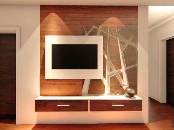 میز تی وی دیواری مدرن به صورت کشویی می باشد و صفحه نمایشگر در قالبی سفید رنگ بر روی بدنه میز به صورت برجسته متصل شده است و رنگ کشو ها به صورت قهوه ای مات و رنگ بدنه میز تی وی دیواری قهوه ای روشن در چیدمان د اخلی منزل می باشد.