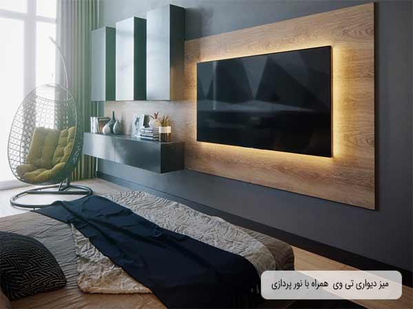 میز دیواری تلویزیون به صورت قفسه باز در اتاق خواب می باشد که تلویزیون بر روی دیواره چوبی میز متصل شده است و پشت آن نورپدازی زرد رنگی شده است و روبه روی آن تخت خواب قرار دارد و قفسه باز میز دیواری بغل صفحه نمایشگر قرار گرفته است که روی آن با لوازم تزیینی پچیدمان شده است و بالای آن سه قفسه بسته مجزا از هم به رنگ مشکی قرار گرفته است