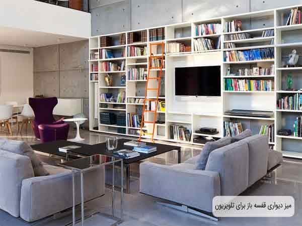 تی وی ست دیواری قفسه باز سفید که در داخل تمام قفسه های آن با لوازم جانبی و تزیینی چیدمان شده است و صفحه نمایشگر به دیواره پشتی سفید میز متصل شده است و یک نردبان نارنجی به میز تکیه داده است و دو مبل راحتی طوسی رنگ در تصویر روبه روی میز دیواری قرار گرفته است و روبه روی مبل ها میز جلو مبلی می باشد که روی آن چندین کتاب قرار گرفته است