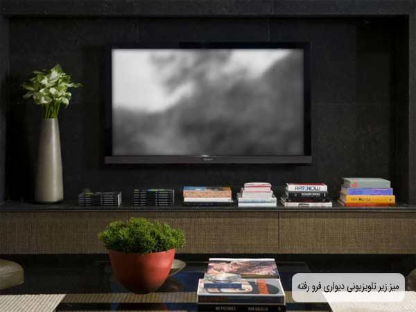 باکس تی وی دیواری قفسه باز و کشویی در تصویر می باشد که نمایشگر در دیوار به صورت فرو رفتگی متصل شده است و رنگ زمینه صفحه تلویزیون خاکستری است و زیر آن تعدادی کتاب و لوازم جانبی دیگری چیدمان شده است و کنار تلویزیون یک گلدان قرار گرفته است و رنگ پشت زمینه تی وی مشکی می باشد