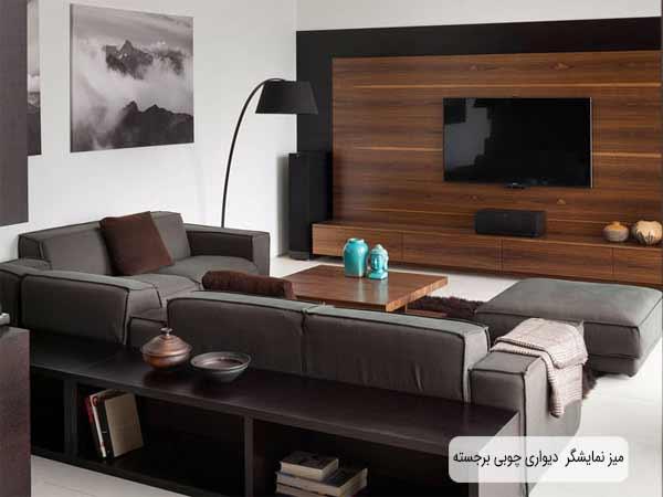 باکس تلویزیون دیواری چوبی بر جسته ای به رنگ قهوه ای تیر در تصویر می باشد که نمایشگر به دیواره میز متصل شده است و اسپیکر آن در زیر آن قرار گرفته است و به رنگ مشکی است و میز دیواری دارای کشو می باشد و زمینه پشتی میز دیوار مشکی رنگ می باشد و رو به روی آن مبلمان راحتی خاکستری تیره ای قرار گرفته است