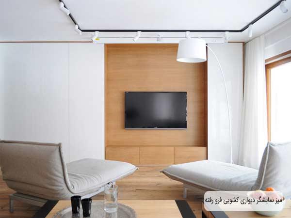میز نمایشگر دیواری چوبی که دارای سه کشو می باشد و به صورت فرو رفته می باشد و تلویزیون بر روی دیواره میز متصل شده است و رو به روی آن دو مبل راحتی سفید قرار گرفته است
