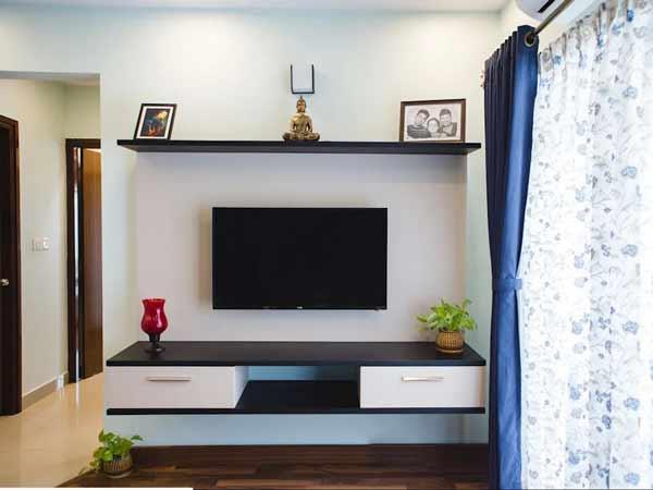 میز زیر تلویزیونی دیواری با ترکیب رنگ های قهوه ای تیره و سفید ذر چیدمان خانه می باشد که به صورت کشویی است و صفحه نمایشگر بر روی دیوار پشتی آن نصب شده است و در قسمت بالای آن یک قفسه باز می باشد که روی آن یک مجسمه طلایی رنگ و دو قاب عکس می باشد.