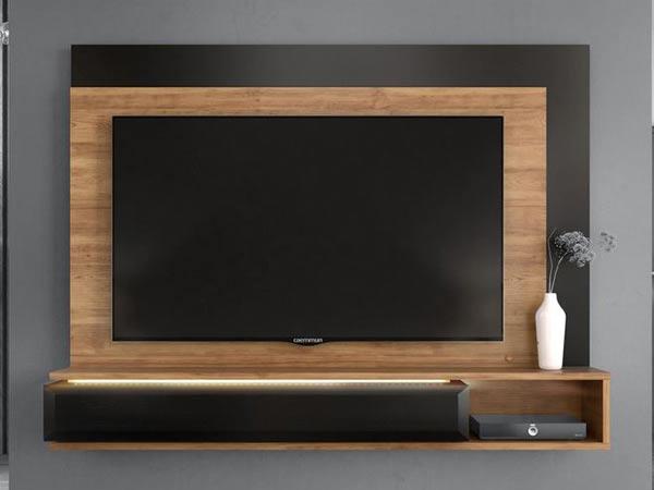 میز نمایشگر دیواری چوبی در دکوراسیون داخلی منزل می باشد که که تلویزیون به دیواره چوبی میز که به رنگ قهوه ای روشن است نصب شده است و روی میز تی وی دیواری یک گلدان سفید رنگی قرار دارد و زمینه دکوراسیون به رنگ طوسی می باشد.