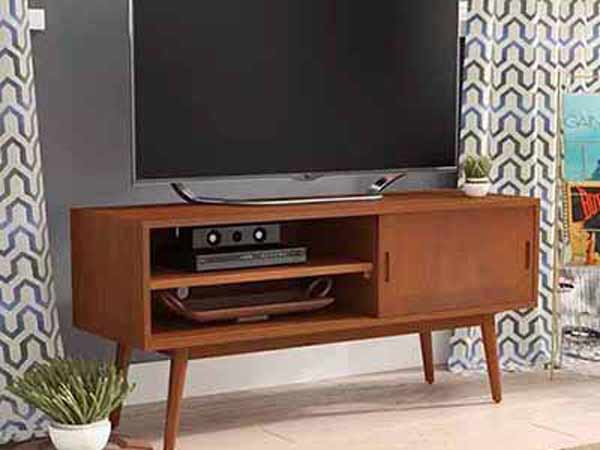 یک صفحه نمایشگر بزرگی روی یک میز زیر تلویزیونی چوبی به رنگ قهوه ای روشن قرار دارد و در کنار میز گلدان سفید رنگی می باشد و در داخل قفسه میز تلویزیون لوازم جانبی آن قرار گرفته است