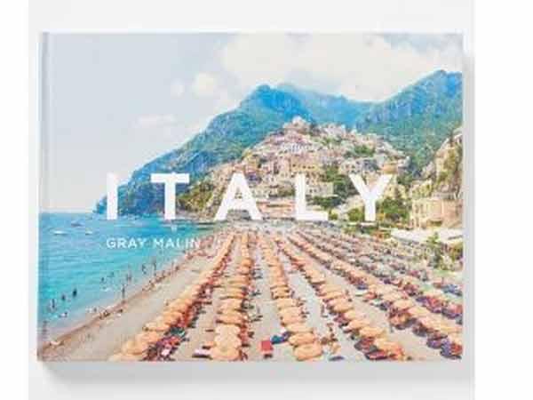 کتابی در تصویر می باشد که عکس روی جلد آن منظره ای از کوه و دریا و ساحل را نشان می دهد و روی آن نوشته ای از ایتالیا می باشد