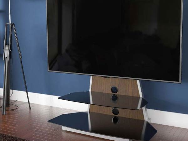 میز تی وی کانتی لور به رنگ قهوه ای در تصویر می باشد که قسمتی از آن از جنس چوب می باشد و صفحه نمایشگر به آن وصل می باشد و این میز به صورت قفسه باز شیشه ای می باشد و پشت میز دیواری به رنگ آبی قرار دارد
