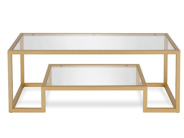 میز جلو مبلی چوبی به رنگ کرم تیره در زمینه ای سفید قرار دارد که روی آن از شیشه می باشد