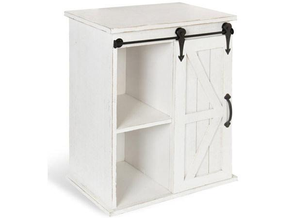میز عسلی چوبی سفیدی به صورت قفسه باز و کابینتی با دستگیره مشکی در زمینه ای سفید از عکس قرار دارد