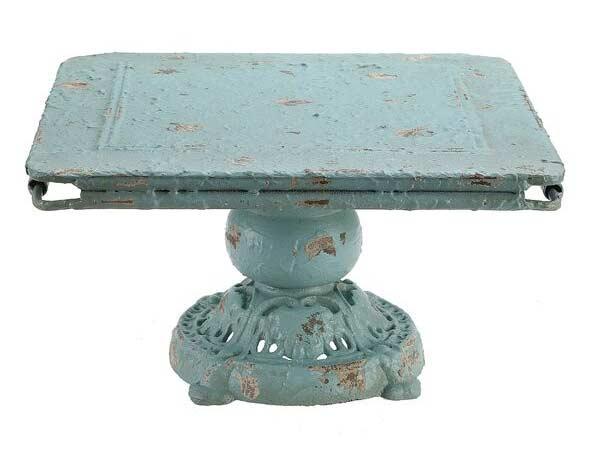 ظرفی انتیک به رنگ فیروزه ای پایه دار گرد که سری آن به صورت مستطیل مانند تخت می باشد در زمینه ای سفید در عکس قرار دارد