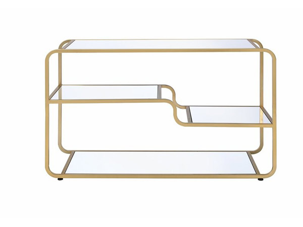 میز تلویزیون طلایی رنگ همراه با قسمتی شیشه ای در زمینه ای سفید از تصویر قرار دارد