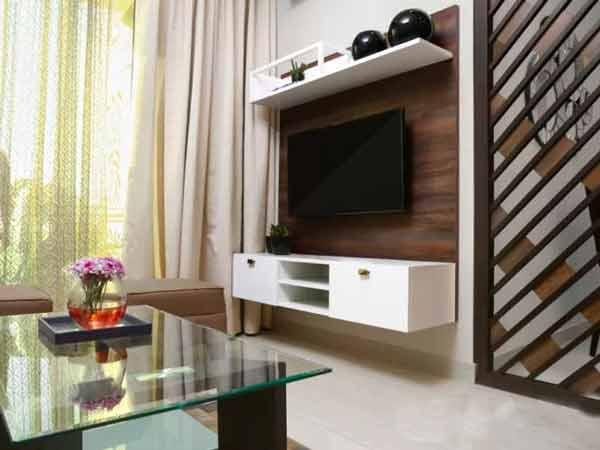 میز تی وی دیواری با بدنه چوبی به رنگ قهوه ای تیره می باشد که تی وی به روی آن نصب شده است و دارای میزی به رنگ سفید می باشد که به بدنه آن متصل است و رو به روی میز تی وی یک میز شیشه ای قرار دارد که روی آن یک گلدان می باشد