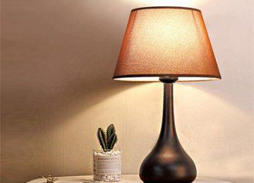 تصویر یک آباژور مدرن رومیزی بر روی یک میز در حال نوردهی در کنار این آباژور مدرن یک عدد کاکتوس مشخص می باشد.