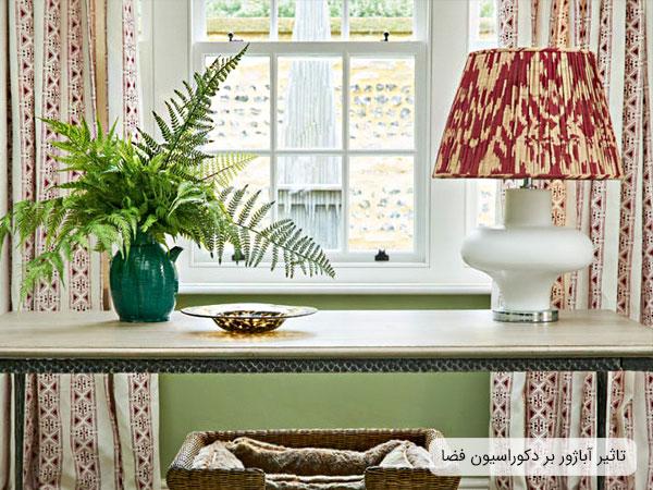تصویری از یک آباژور بر روی اوپن آشپزخانه در کتار یک گلدان که فضای بسیار زیبایی برای دکوراسیون داخلی خانه به ارمغان آورده است