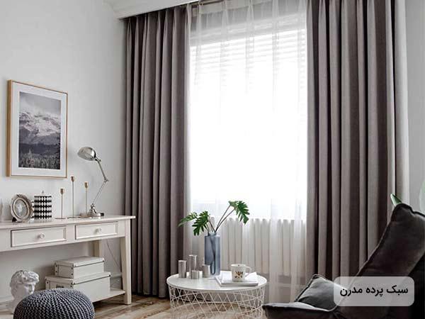 تصوير يک پرده بلند مدرن ساده با چين هاي زیاد و به رنگ خاکستري به همراه یک مبل و قاب عکس و یک میز کوچ دایره ای شکل