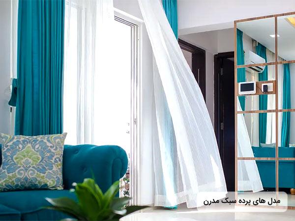 عکس پرده مدرن آبي و سفيد رنگ در فضاي داخلي پذيرايي . تصوير مبل راحتی آبی رنگ روي آن يک عدد کوسن قرار دارد.