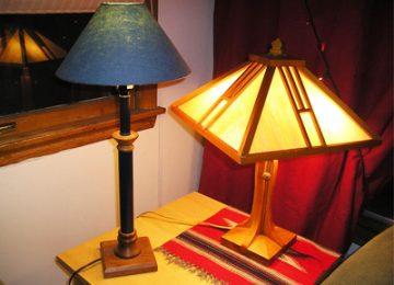 دوعدد آباژور در تصویر مشخص می باشد که کلاهک یکی از آنها عبور دهنده نور و دیگری مانع نور می باشد. در پس زمینه تصویر یک تابلو بر روی دیوار و میز نگه دارنده آباژور ها نمایان می باشد.