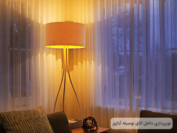 یک عدد آباژور در گوشه یک اتاق که باعث شده نورپردازی فضا هرچه بهتر انجام گیرد. همچنین این نور پردازی باعث شده تا میز عسلی کنار مبل و کوسن های آن بخوبی دیده بشوند.