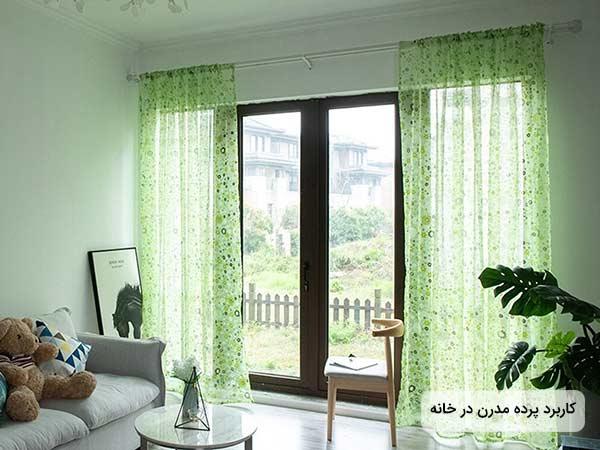 عکس پرده حرير سبک مدرن سبز رنگ که روي پنجره چوبي بزرگي نصب شده استبه همراه يک مبل راحتي خاکستري رنگ و يک خرس عروسکي و تعدادي کوسن روي مبل وسط اتاق يک ميز گرد قرار داردجلوي پنجره قدي يک صندلي چوبي قابل مشاهده است