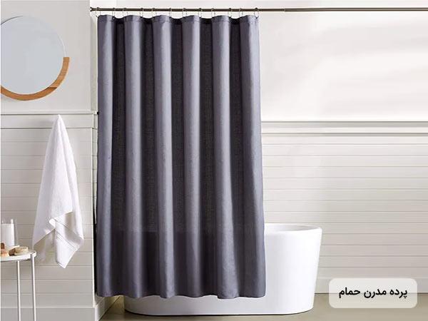 تصوير پرده حمام سبک مدرن به رنگ بنفش و پشت پرده وان حمام سفيد قرار دارد. روي دويار آينه و حوله آويزان شده است. رنگ حوله سفيد است