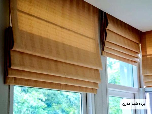عکس پرده شيد رولي قهوه اي رنگ روي پنجره بيرون پنجره فضاي سرسبزي قابل مشاهده است
