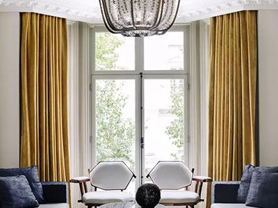 عکس دو عدد پرده سبک مدرن زرد رنگ که بر روي يک پنجره بزرگ قرار دارد. در تصوير چهار عدد مبل راحتي به رنگ سورمه اي و سفيد وجود دارد. يک ميز گرد وسط نيز جلوي مبل قرار گرفته است. يک عدد لوستر در بالاي تصوير وجود دارد.
