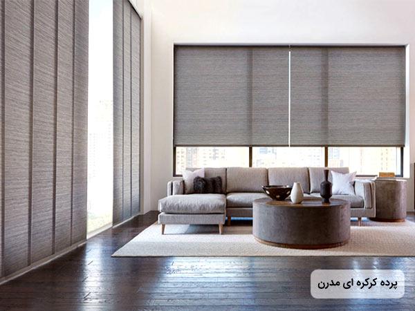 عکس پرده کرکره اي خاکستري رنگ روي يک ديوار بلند با پنجره بزرگ به همراه يک مبل ال شکل خاکستري و يک ميز دايره اي شکل از جنس چوب و پارچه .