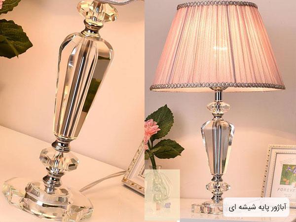 آباژوری سبک مدرنی با پایه های شیشه ای بر روی میز به همراه گل و قاب عکس .