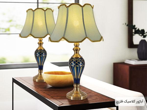 آباژور سنتی فلزی بر روی میز در کنار پنجره