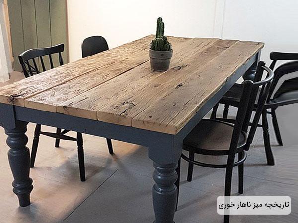 تصویر یک میز ناهار خوری به همراه صندلی های اطرافش ؛ میز ناهار خوری قدیمی و چوبی می باشد.