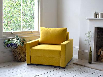 تصویر یک صندلی تختخواب شو زرد رنگ در فضای دکوراسیون منزل در کتار پنجره