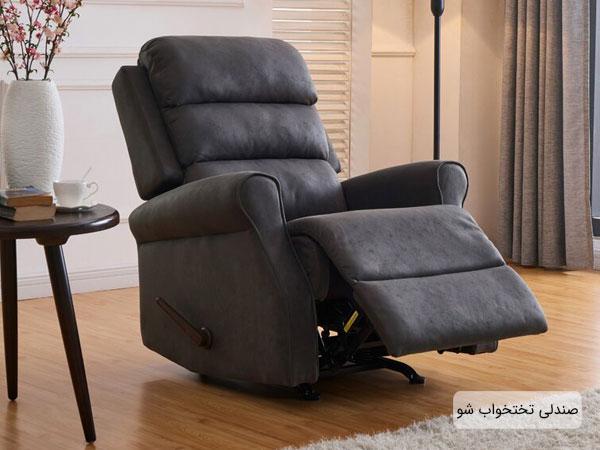 تصویر یک صندلی تخت خواب شو تکی در کنار دکوراسیون داخلی منزل، با رنگ مشکی