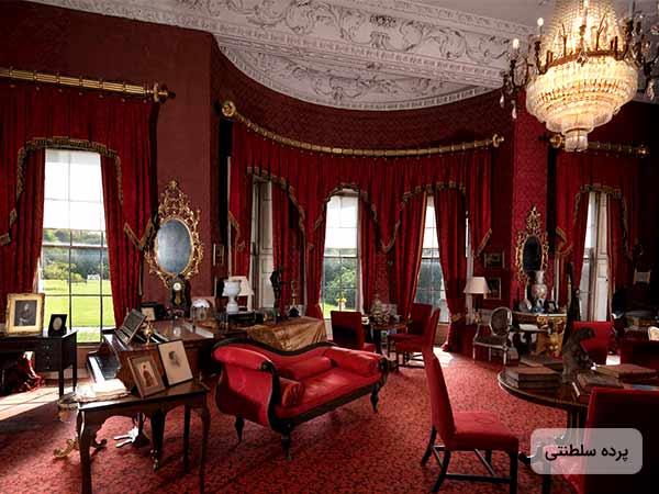 عکس سه عدد پرده سلطنتي قرمز به همراه چوب پرده هاي طلايي رنگ و مبلمان به رنگ قرمز و يک آينه روي ديوار و يک لوستر سلطنتي روي سقف