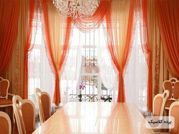 عکس پرده کلاسيک نارنجي با آستر سفيد و يک ميز ناهارخوري بزرگ و تعدادي صندلي کنار آن