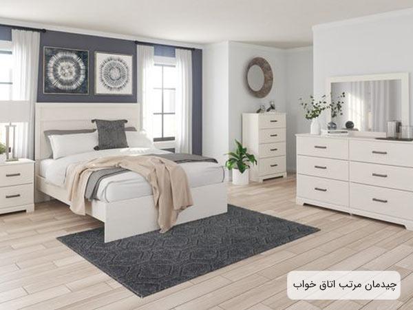 محيط يک اتاق خواب که شامل يک تختخواب دو نفره، يک عدد ميز کنار مبلي، دراور ها، فرش و ساير لوازم دکوري مي باشد